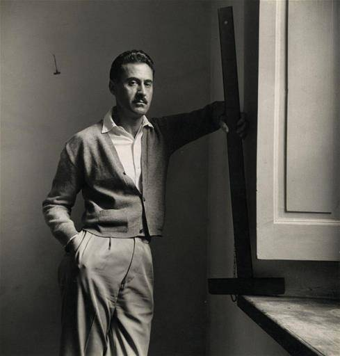Franco Albini photographed near a window with a framing square in his hand.