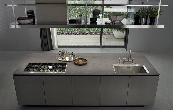 Sink and working surface of the Artex kitchen and shelves in grey steel on top.